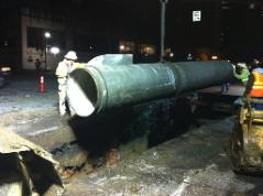 Crew lowers pipe into trench