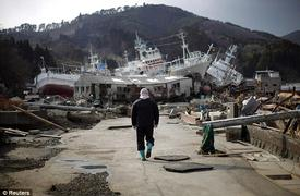 Devastation: A man walks next to port area destroyed by the earthquake and tsunami in Kessenuma town, in Miyagi prefecture. CREDIT: Reuters