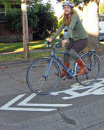 Woman biking on a neighborhood greenway.