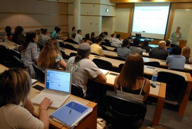 classroom of students look on to professor and screen at front of class