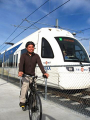 Person on bike next to MAX light rail