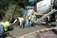 Crew building sidewalk with curb ramp