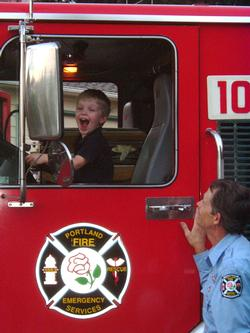 Little boy grinning in fire truck
