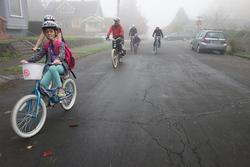 Families bike riding on a foggy winter morning