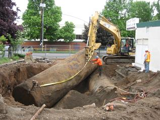 workers remove an underground fuel storage tank from a former gas station