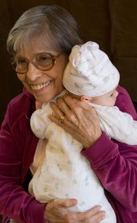 Picture of an elderly woman holding a baby