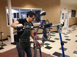 Volunteer adjusting a bike at Fix It Fair