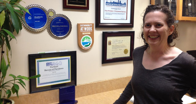 staff member next to recognition plaque