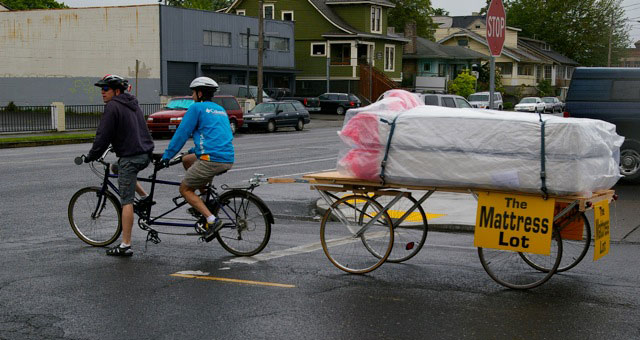 Two people delivering a mattress by bike.