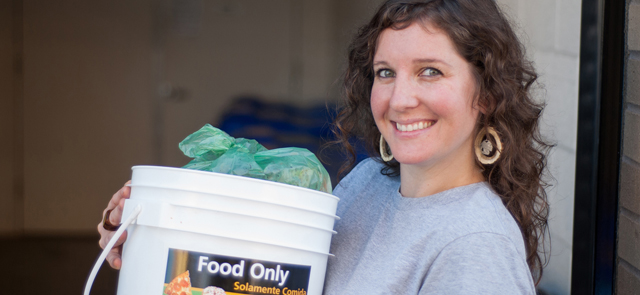 Woman holding food scraps bucket