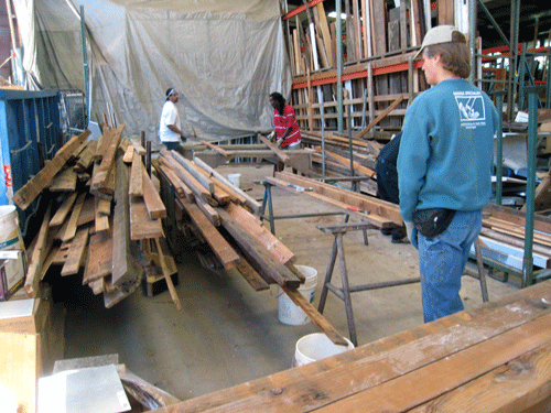 workers organize reclaimed lumber