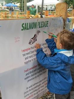 child signing salmon pledge poster