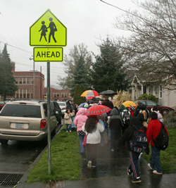 Kids walk to school next to cars at curb