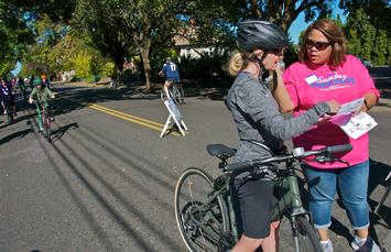 Sunday Parkways volunteer shows woman a map