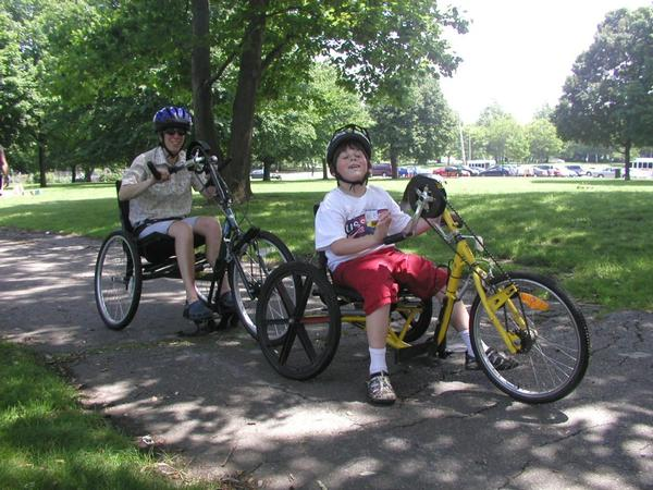 Two people riding adaptive bikes in a park.