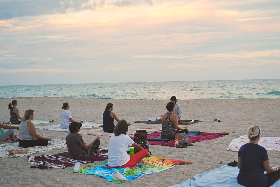 Vacationers doing yoga on the beach
