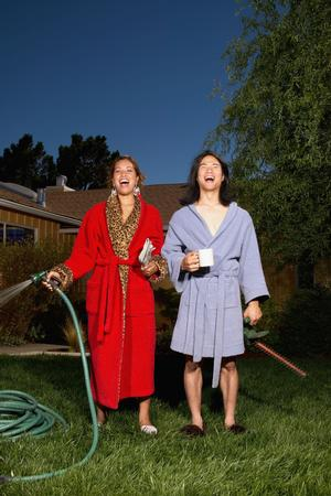Couple watering lawn in their pajamas