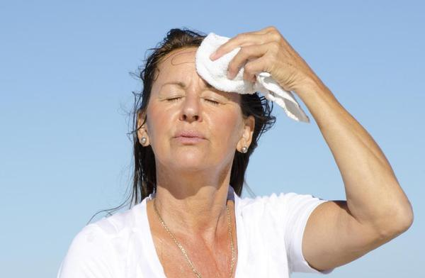 Photo of Woman drying her forehead on hot day