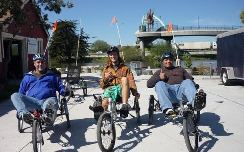 Photo of three people riding adaptive bikes