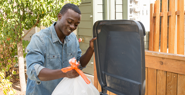 man putting garbage in gray roll cart