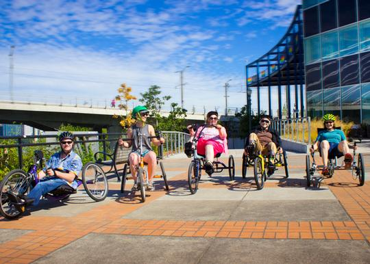 Five riders on adaptive bikes facing the camera.