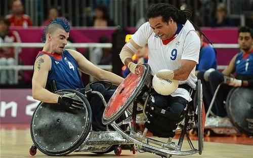 Two people playing wheelchair rugby. One is holding the ball and has their chair balanced on the footrest of the second player. They have intense looks on their face and may be shouting.