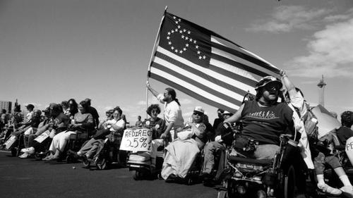 Group of people rallying for disability rights. A US flag with is held up, the stars depicting the International Symbol of Accessibility instead of the usual 50 stars.