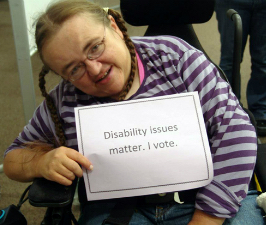 Voter holding sign reading Disability issues matter, I vote.