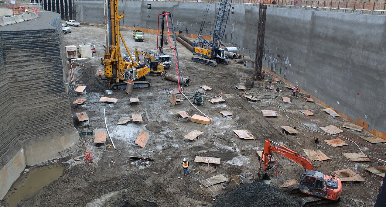 Construction site with large equipment and wood sheets covering large holes