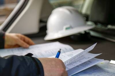 Person with paperwork and hard hat on a desk.