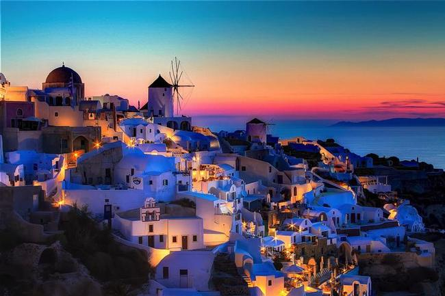 Photo of a Santorini hillside by an ocean at sunset.