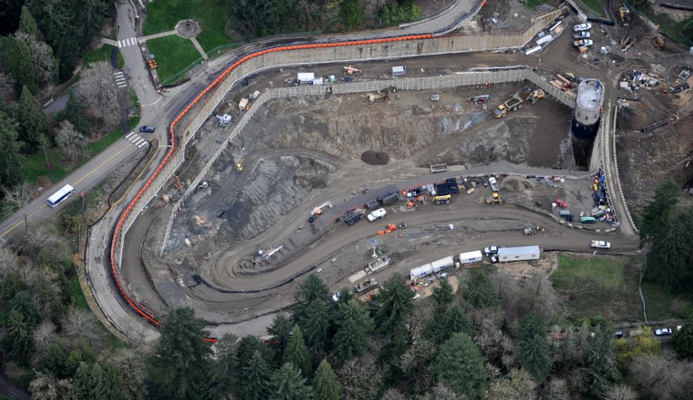 An aerial view of a large in-ground reservoir with construction trucks situated in the basin. The site is surrounded by evergreen trees