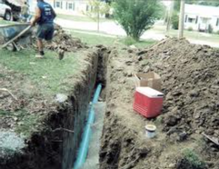Trench in ground with sewer pipe being installed.