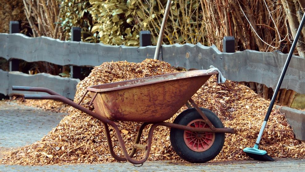 Wheelbarrow next to a pile of mulch nuggets