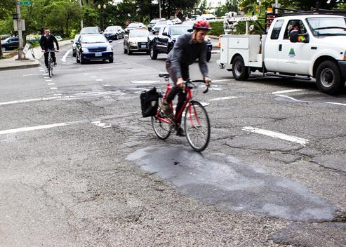 Person rides bicycle on poor pavement on SW Main Street