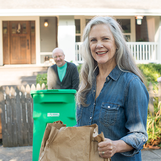 white woman smiling with brown bag lunch