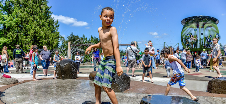 Several smiling children play with sprays of water coming from the splash pad at Spring Garden Park.