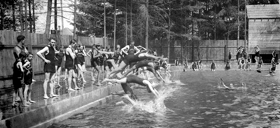 Original Peninsula Park Pool from 1921 - black and white image of young men and boys standing on the side of pool with tall wood fence behind.