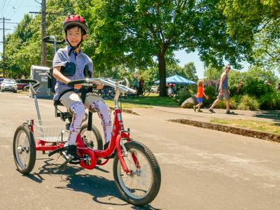 Happy child riding an adaptive bike at Sunday Parkways North 2018