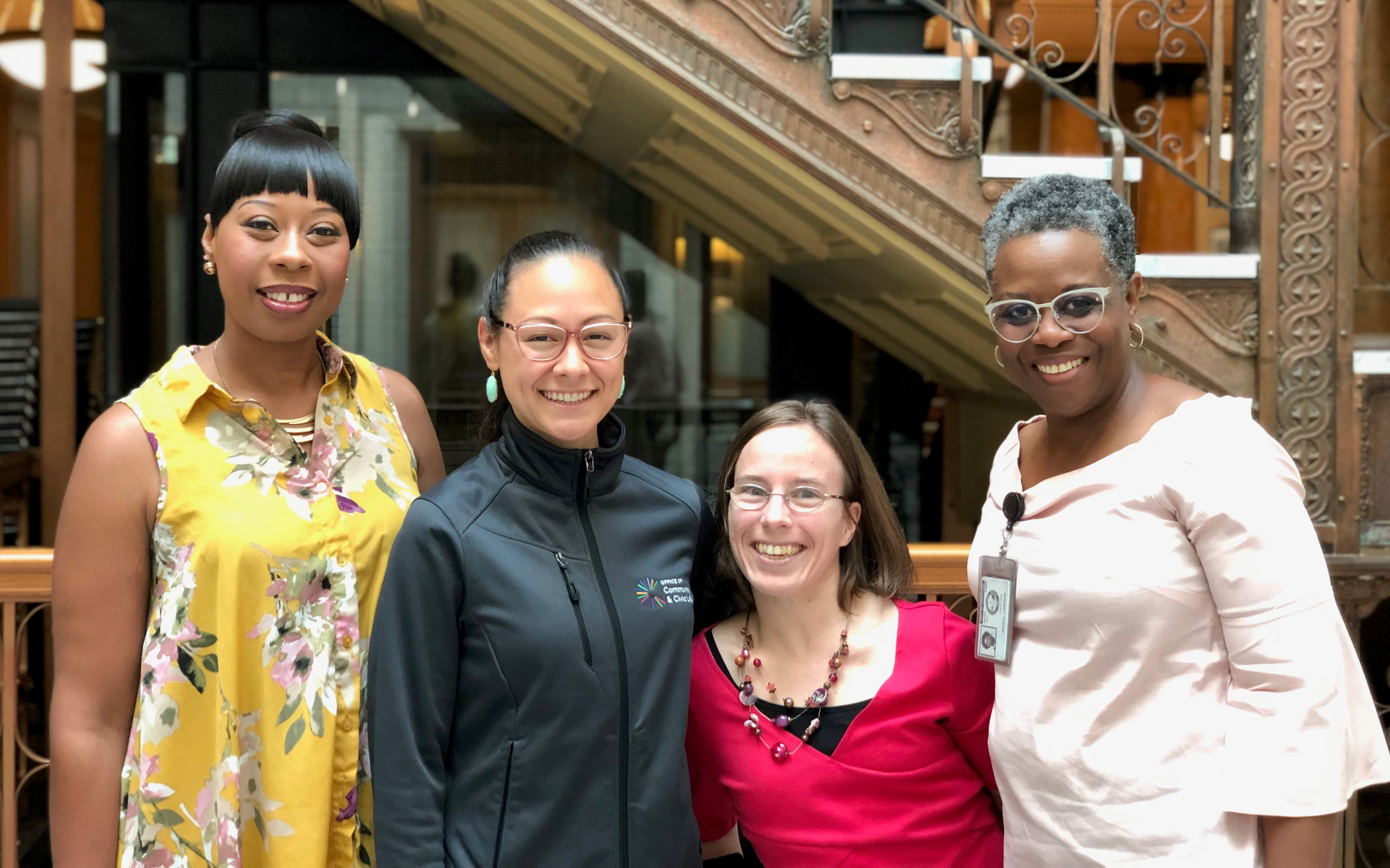 Group photo of Tyesha McCool-Riley, Ashley Tjaden, Joanne Johnson, and Lorraine Wilson, arms around each others' shoulders, facing the camera and smiling. Behind them, the ornate elevator and staircase in City Hall is visible.