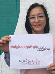 woman with sign digital equity is access without barriers