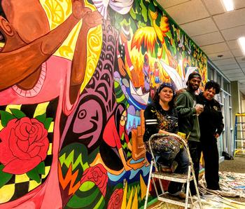 A picture of the artists and the fire chief in front of a brightly colored wall mural