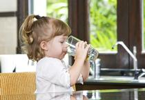 Toddler girl taking a drink of water from a glass.