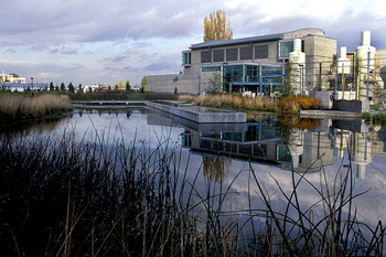 Photo of headworks building with pong and wetlands and native plants featured in front. The headworks building provides preliminary treatment of wastewater by removing debris, grit, and sand from the flow with large screens.