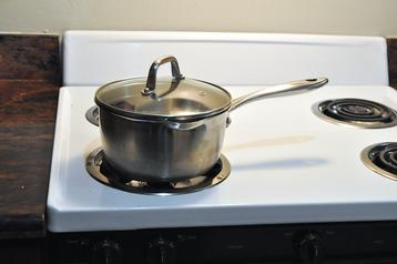 A pot handle turned inwards on a stovetop