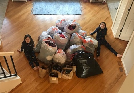 Two children sitting amongst a mountain of coats in bags