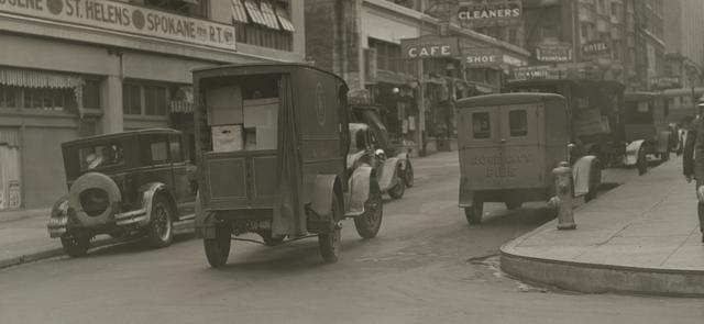 black and white photo of old fashioned cars on city street
